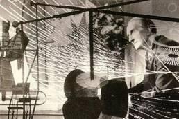 """Duchamp fotografato da Mark Kauffman dietro al suo """"Grande Vetro"""""""