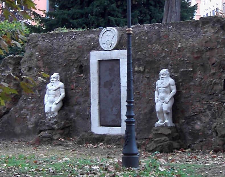La Porta Magica di Roma oggi con a fianco le due sculture di Bes