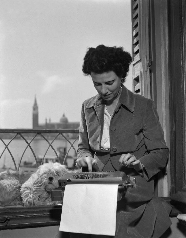 Peggy Guggenheim alla macchina da scrivere nella sua stanza all'hotel Savoia & Jolanda, Venezia 1948