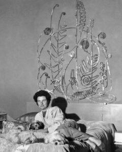 Peggy Guggenheim nella sua camera da letto a Palazzo Venier dei Leoni posa sotto la testiera in argento di Alexander Calder, Venezia primi anni Cinquanta